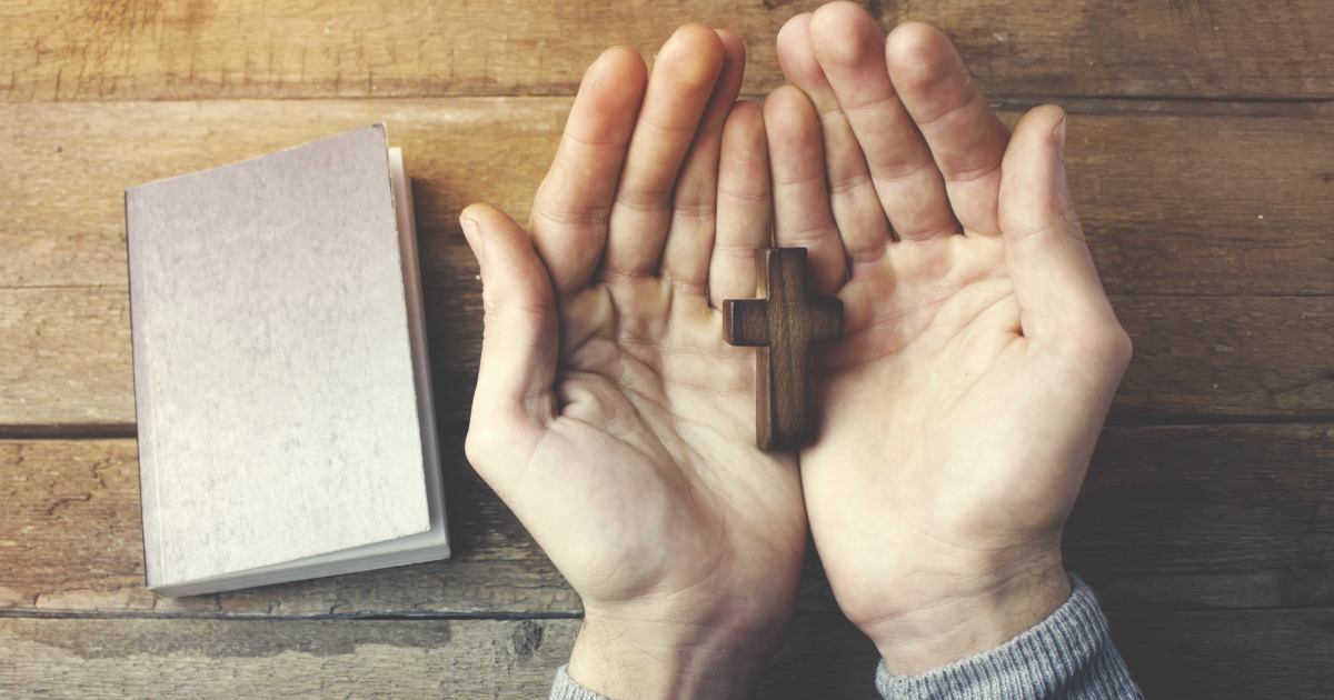 Hands of praying young man and Bible