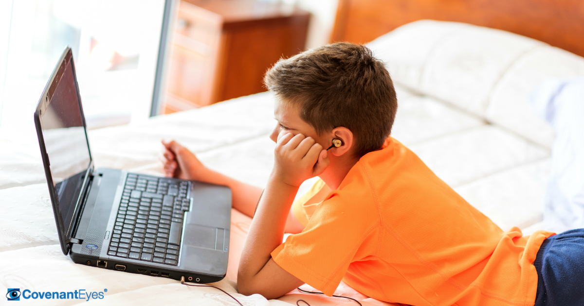 young boy watching computer on bed